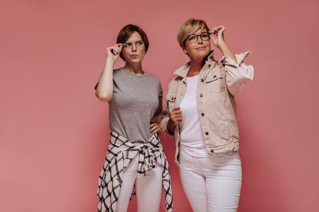 Duas mulheres elegantes de cabelos curtos com óculos em calças justas brancas e camisetas legais posando em fundo rosa isolado.