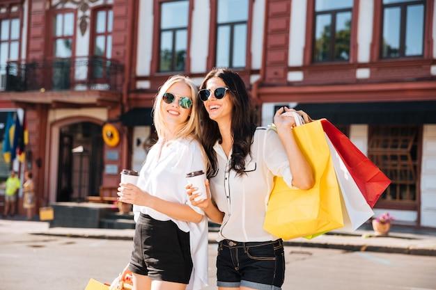 Duas mulheres elegantes e felizes andando na rua da cidade segurando sacolas de compras