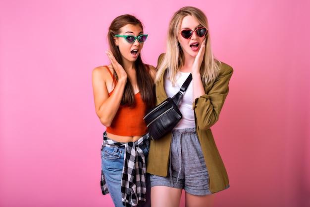 Duas mulheres elegantes e hipster, melhores amigas, irmãs, meninas, se abraçando e sorrindo