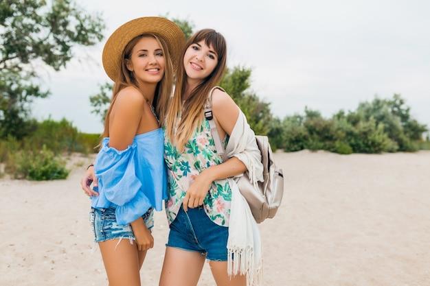 Duas mulheres elegantes e muito sorridentes em férias de verão, amigos viajam juntos, moda praia moda