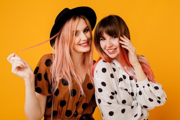 Duas mulheres elegantes elegantes em vestidos posando sobre parede amarela