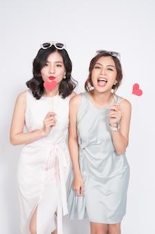 Duas mulheres elegantes em belos vestidos juntas e segurando a forma de um coração vermelho.