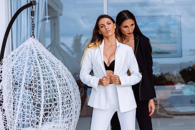 Duas mulheres elegantes em ternos pretos e brancos em pé do lado de fora da villa, em uma parede de vidro