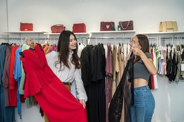 Duas mulheres em boutique fashion escolhem vestido. descontos de férias da temporada para fazer compras. sexta-feira preta