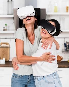Duas mulheres em casa se divertindo com fone de ouvido de realidade virtual