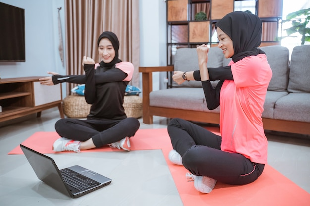 Duas mulheres em hijab sportswear sentadas de pernas cruzadas aquecendo com uma mão segurando a outra enquanto uma mão é puxada para o lado enquanto fazem atividades juntas em casa