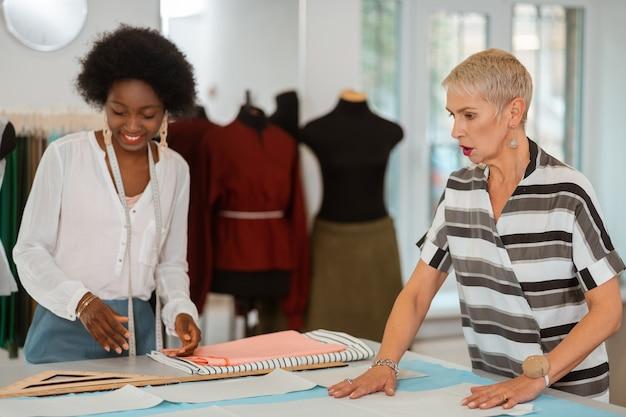 Duas mulheres em pé ao lado da mesa e colocando os padrões de papel no tecido em uma oficina