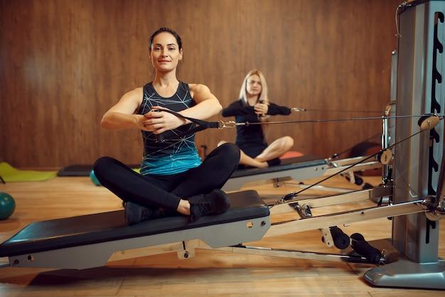 Duas mulheres em pilates treinando na máquina de exercícios no ginásio, flexibilidade.