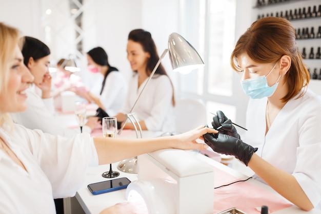 Duas mulheres em procedimento de manicure, salão de beleza