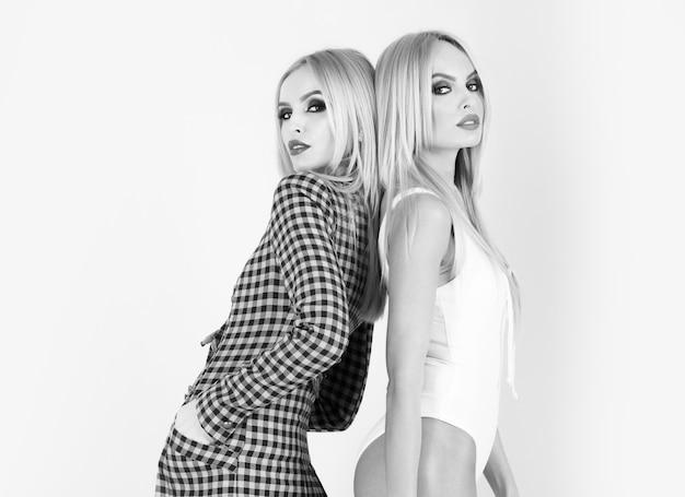 Duas mulheres em roupas de moda, amigas muito loiras, irmãs gêmeas com maquiagem brilhante.