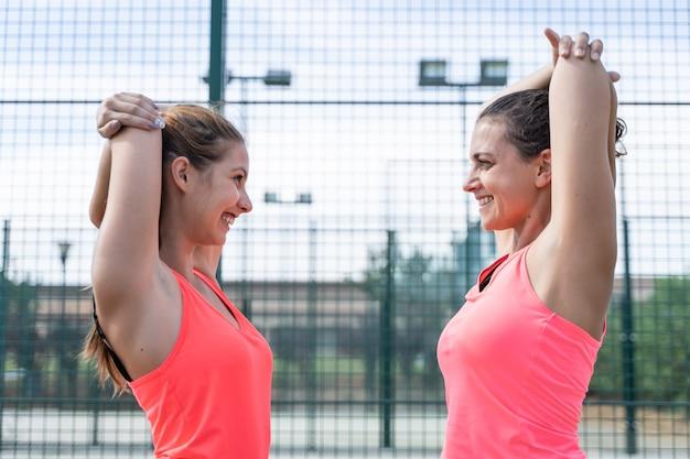 Duas mulheres em roupas esportivas, esticando os braços na frente do outro em uma quadra de tênis