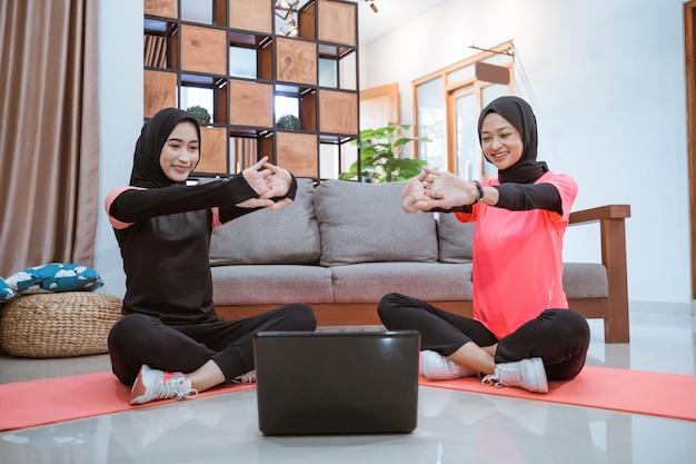Duas mulheres em roupas esportivas hijab sentadas no chão, aquecendo, esticando os braços para a frente, enquanto fazem atividades juntas em casa