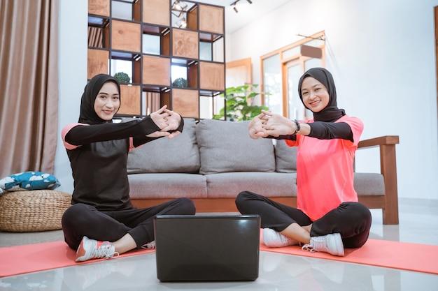 Duas mulheres em roupas esportivas hijab sorriem sentadas no chão, aquecendo, esticando os braços para a frente, enquanto fazem atividades juntas em casa