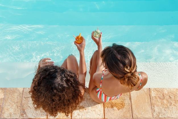 Duas mulheres em trajes de banho relaxando e bebendo coquetéis tropicais na vista de cima da piscina. Foto Premium