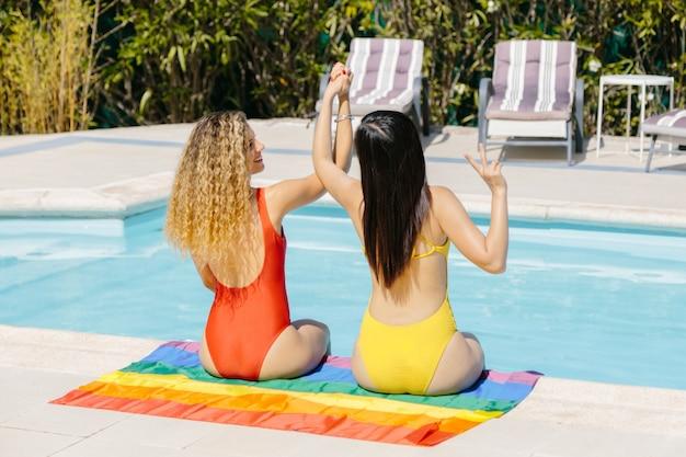 Duas mulheres em trajes de banho sentados na beira de uma piscina acima de uma bandeira lgtb