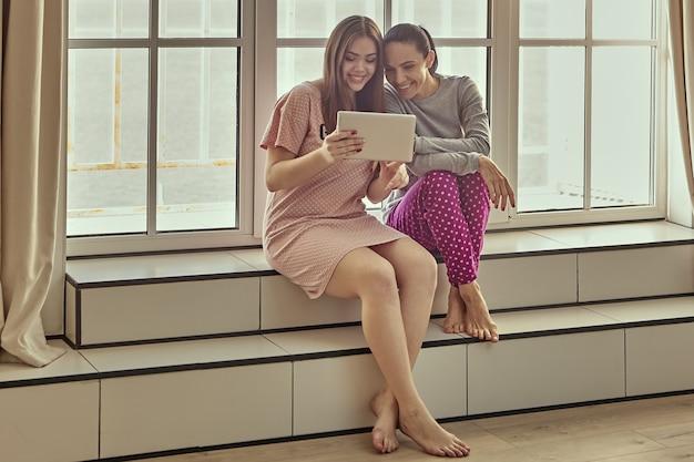 Duas mulheres em trajes de dormir estão sentadas no parapeito da janela e assistindo a um vídeo engraçado na tela do tablet pc