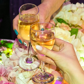 Duas mulheres em um bar tilintam taças com vinho branco. conceito - encontro de amigos, feriado feminino, festa de despedida de solteiro