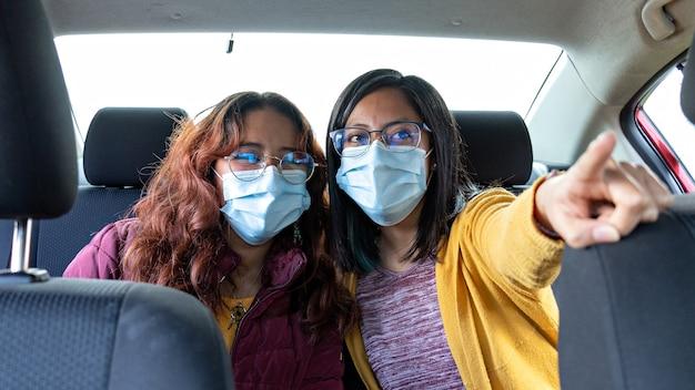 Duas mulheres em um carro usando máscaras apontando para o ponto de chegada