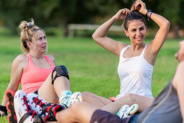 Duas mulheres em um grupo de amigos sentadas em um parque com patins