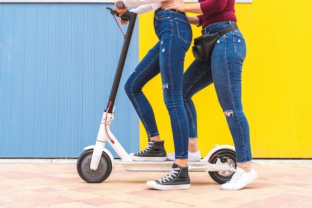 Duas mulheres em uma scooter elétrica sobre amarelo e azul.