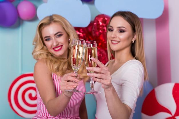 Duas mulheres em vestidos cor de rosa segurando taças de champanhe.