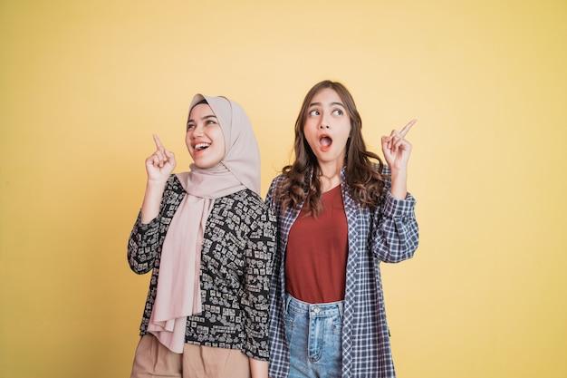 Duas mulheres empolgadas em pé lado a lado com gestos de dedo apontando para cima com copyspace