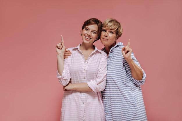 Duas mulheres encantadoras com penteado curto na moda em vestido elegante listrado, sorrindo, abraçando e mostrando para colocar o texto no fundo rosa.