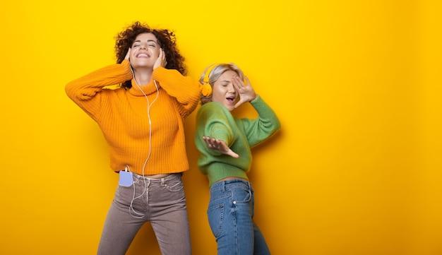 Duas mulheres encantadoras dançando em uma parede amarela com espaço livre ouvindo música com fones de ouvido