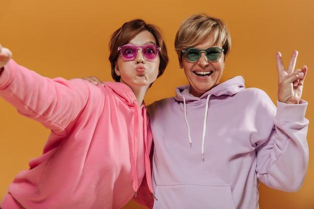 Duas mulheres engraçadas com penteado curto moderno em óculos de sol brilhantes e legais e capuz rosa e lilás tomando selfie e se divertindo em um fundo laranja.