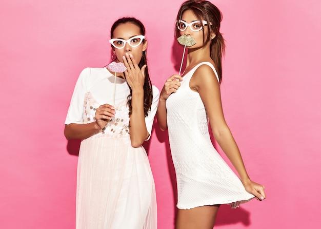 Duas mulheres engraçadas surpresos em copos de papel e lábios grandes na vara. conceito de beleza e inteligente. alegres jovens modelos prontos para a festa. mulheres isoladas na parede rosa. fêmea positiva