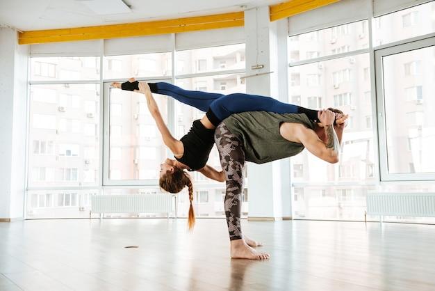 Duas mulheres, equilibrando e fazendo acro yoga no estúdio