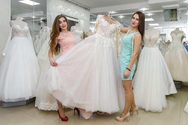 Duas mulheres escolhendo vestido de noiva na loja