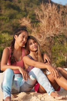 Duas mulheres esportivas têm expressões pensativas à distância, posam na natureza