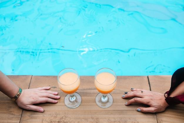 Duas mulheres estão bebendo suco de laranja à beira-mar.