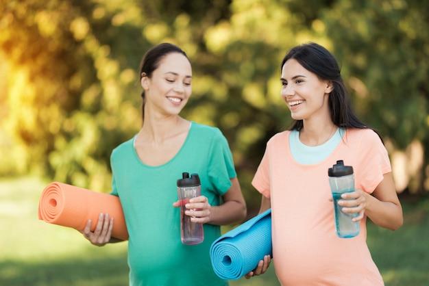 Duas mulheres estão de pé no parque com esteiras de ioga.
