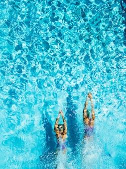 Duas mulheres estão nadando em uma piscina, vista de cima.