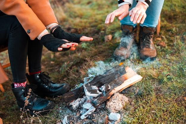 Duas mulheres estão se aquecendo perto de uma lenha em um campo