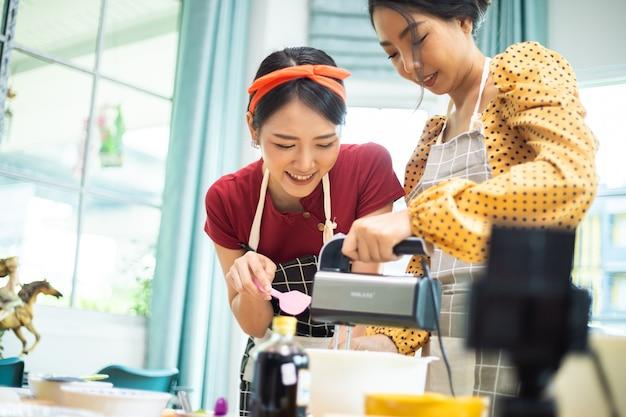 Duas mulheres estão trabalhando juntas para preparar algo na aula de culinária.