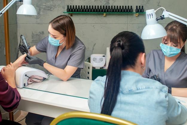 Duas mulheres fazendo as unhas de duas manicures em um salão de beleza