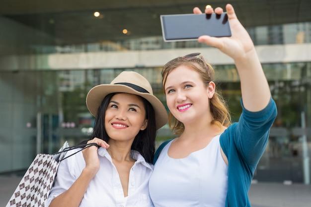 Duas mulheres fazendo compras e fazendo foto de selfie