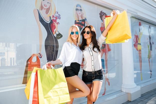 Duas mulheres fazendo compras no centro da cidade com sacolas coloridas e se divertindo
