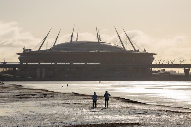 Duas mulheres fazendo esqui caminhando em frente ao enorme estádio zenit em são petersburgo, rússia.