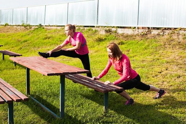 Duas mulheres fazendo exercícios de ginástica ao ar livre antes do treino