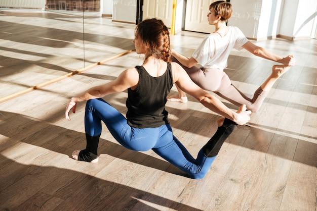 Duas mulheres fazendo exercícios de ioga no chão no estúdio