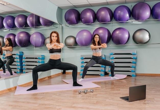 Duas mulheres fazendo exercícios esportivos na sala de ginástica com bolas