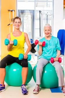 Duas mulheres, fazendo, força, desporto, em, ginásio aptidão