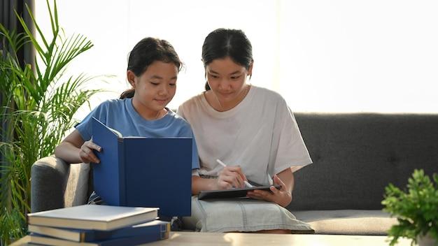 Duas mulheres fazendo lição de casa em casa.