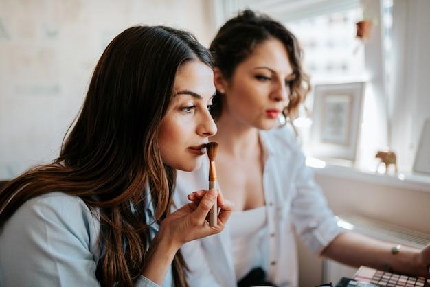 Duas mulheres fazendo maquiagem dentro de casa no apartamento.