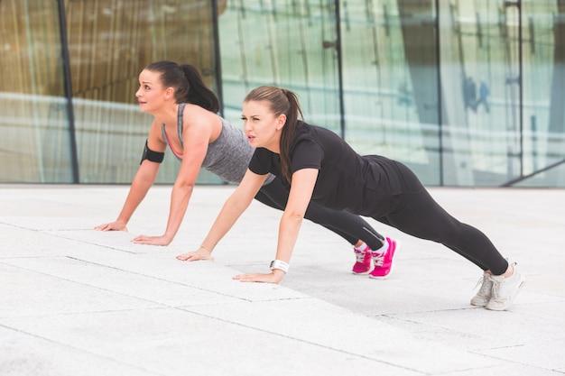 Duas mulheres, fazendo, push-ups, exercícios