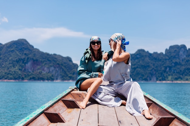 Duas mulheres felizes, blogueiras, turistas, em terno de seda, lenço e óculos escuros, viajam pela tailândia em um barco asiático, o parque nacional khao sok